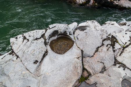 Volcanic rock on the shore of the Upper Rogue River that has been carved by swirling gravel to create holes.