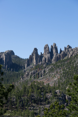 A mountain eroded to expose spires of tall quartz rock among a forest in Custer State Park, South Dakota. Stock Photo