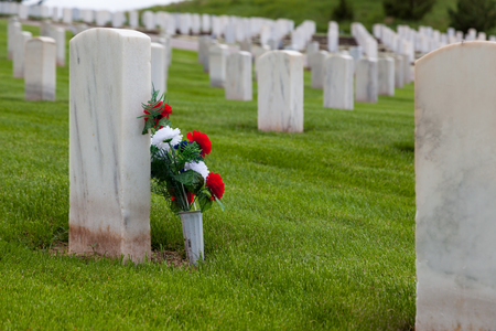 A group of red white and blue flowers leaning against a marble headstone in a military graveyard with vibrant spring grass on a hillside.