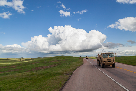 Two National Guard vehicles driving through Wind Cave National Park with rolling green prairie and a large storm cloud in the distance.