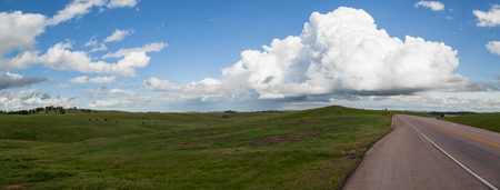 A panoramic view of a spring green prairie next to the road through Wind Cave National Park with ominous storm clouds in the distant sky.