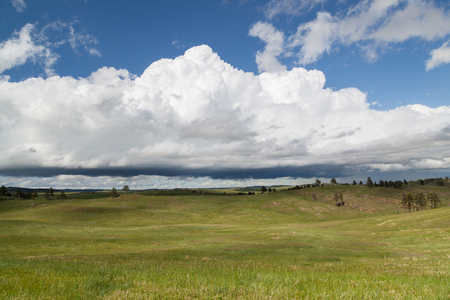 The dynamic landscape of Wind Cave National Park hills and prairie with an ominous looking storm above. Stock Photo