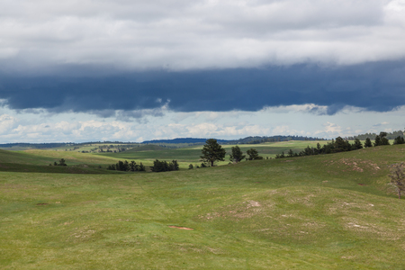 The dynamic landscape of Wind Cave National Park hills and prairie with an ominous looking storm above.