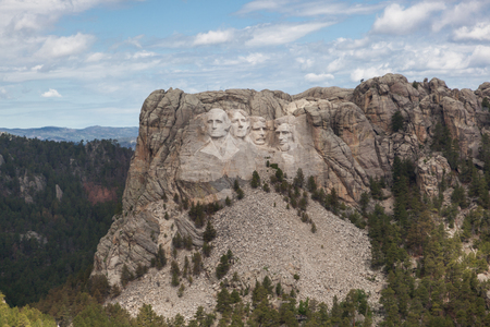 An aerial view of Mount Rushmore Narional Memorial showing the carved faces of past Presidents George Washington, Thomas Jefferson, Theodore Roosevelt, and Abraham Lincoln.