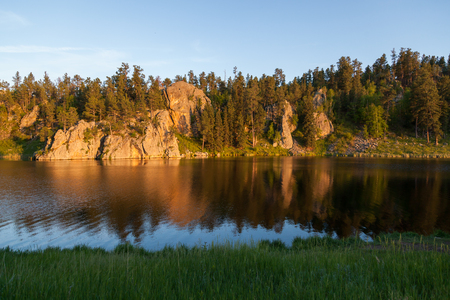 Golden sunshine in the late afternoon shines on a quartz rock formation and creates a soft reflection at Stockade Lake in Custer State Park, South Dakota.
