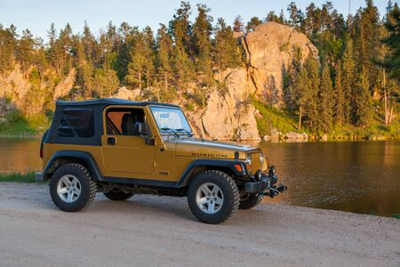 BLACK HILLS, SOUTH DAKOTA - June12, 2014: A 2003 Inca gold Jeep Rubicon parked next to a lake with the late afternoon sun hitting the rocks of the Black Hills, SD on June 12, 2014.