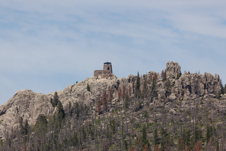 Black Elk Peak ( formerly Harney Peak) and tower which overlooks eroded rock formations and a dying forest in Custer State Park, South Dakota.