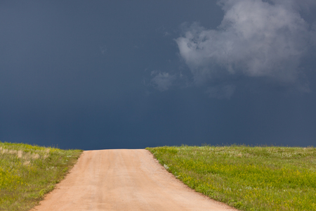 A dirt road leading up a hill that is in bright sunshine with a dark thunderstorm in the distant sky giving a stark contrast. Stock Photo