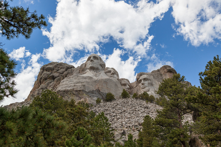 Blue sky and white fluffy clouds provide a striking back drop for the carved faces of four famous United States Presidents in Mount Rushmore National Memorial.