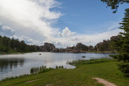 People in small boats enjoy the calm waters of Sylvan Lake with its dynamic granite rock features on the distant shore.