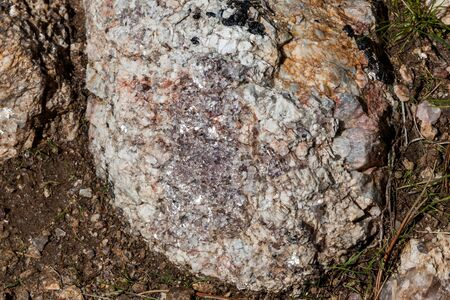 A large rock embedded in the ground that is a composition of quartz crystal, granite, and mica that sparkles in the sunshine.