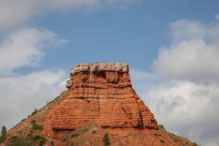 Red clay capped by harder white rock forms a large hill that is eroding over time to expose its layers and cracks with a blue sky and white fluffy cloud background. 스톡 콘텐츠