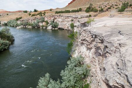 Travertine and gypsum layers left from many years of hot mineral water flow now form an embankment along the Bighorn River in Thermopolis, Wyoming.