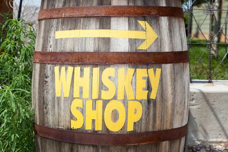 An old whiskey barrel with rusted bands is painted with the words whiskey shop and an arrow pointing the direction. Stok Fotoğraf