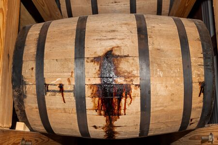 A wooden whiskey barrel leaking bourbon through the slats as it sits on a wooden rack to age. Stok Fotoğraf