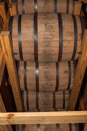 Whiskey barrels full of alcohol are stacked into a wooden holding rack so the bourbon inside can age.
