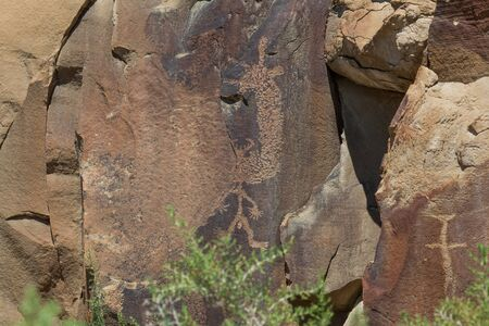 Ancient petroglyphs of  man like figure are carved into sandstone rocks which are cracking and breaking over time at Legend Rock State Petroglyph Site in Wyoming.