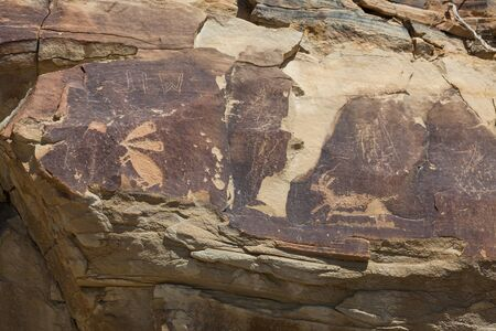 Ancient petroglyphs of a rabbit and a antelope are carved into sandstone rocks along with some more modern graffiti at Legend Rock State Petroglyph Site in Wyoming. Stok Fotoğraf