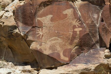 An ancient petroglyphs of a strange creature on a sandstone rock with more modern graffiti from 1834 next to it at Legend Rocks State Petroglyph Site in Wyoming.