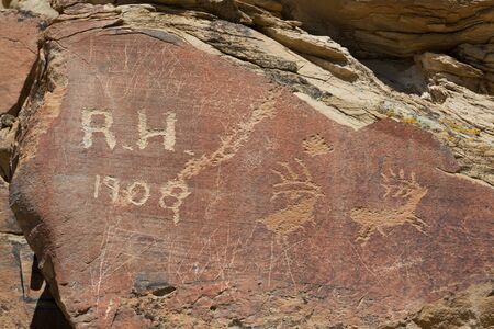 Modern graffiti that is over a hundred years old on a sandstone rock with animal petroglyph carvings that are thousands of years old. Stock Photo