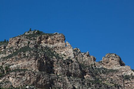 A rock arch high up on the cliff wall on Ten Sleeps Canyon in Wyoming on a clear sunny day.