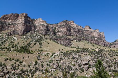 The beautiful landscape of Ten Sleep Canyon on Route 16 in Wyoming with tall rock cliffs green brush and trees and a clear blue sky.
