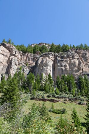 Large sandstone rock that has been carved out by erosion with tall trees and brush and a blue sky in Ten Sleeps Canyon, Wyoming. Stok Fotoğraf
