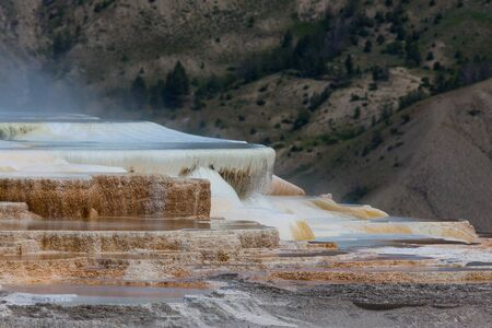 Hot mineral water cascading over stalactite formations with steam rising against the mountains at Yellowstone National Park. Banco de Imagens