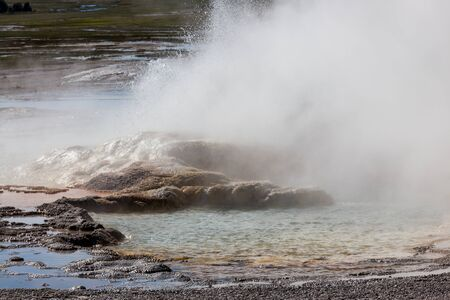 The formation of Clepsydra Geyser as its shoots hot water and steam into the air at Yellowstone National Park, Wyoming. Stok Fotoğraf