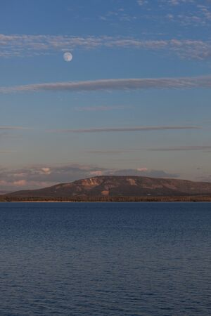 A full moon rising over Yellowstone Lake as the setting sun lights up the surrounding mountains at Yellowstone National Park, Wyoming.