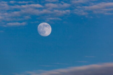 The full moon in a twilight blue sky reflecting the setting sun above Yellowstone National Park, Wyoming.