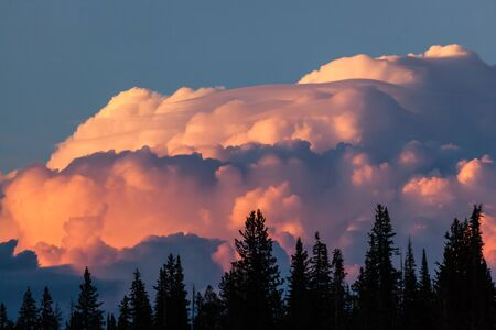 Very large and dynamic storm clouds gather over the mountains surrounding Yellowstone National Park and are lit up by the setting sun.