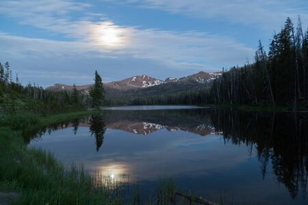 The full moon over Top Notch Peak is reflecting light onto Sylvian Lake in Yellowstone National Park, Wyoming in a long exposure. Stok Fotoğraf