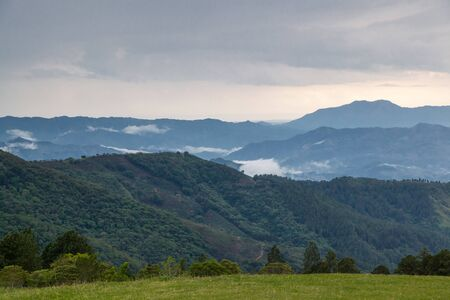 View of the valleys and mountains in Costa Rica form the mountains near Santa Ana with clouds and fog at the distance.
