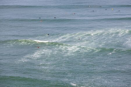 A multitude of unidentifiable people enjoying the waves as they surf in full wet suits in the cold waters of the South American Pacific in Lia, Peru.