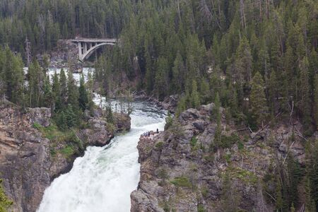The Upper Falls of the Yellowstone River with unidentifiable tourist on an overlook and the South Rim Drive bridge in the distance at Yellowstone National Park, Wyoming. Stok Fotoğraf