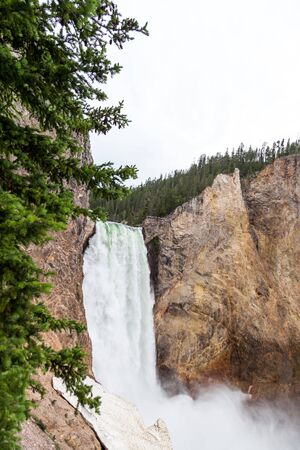 The tall and powerful Lower Falls of the Yellowstone River as it falls into the steep canyon with unidentifiable people on a viewing platform near the top in Yellowstone National Park, Wyoming.