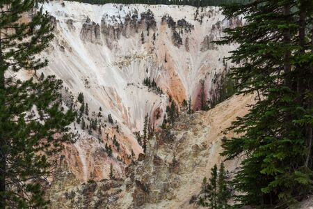Steep canyon walls that have been eroded over time exposing the colorful rocks as seen from Artists Point at the Grand Canyon of the Yellowstone in Yellowstone National Park, Wyoming. Stok Fotoğraf