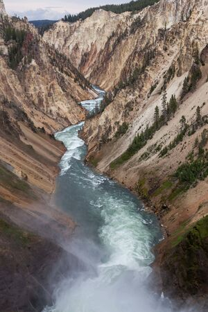 Looking down the Yellowstone River from the top of Lower Falls as mist rises and the rapids cut a path through the Grand Canyon of the Yellowstone at Yellowstone National Park, Wyoming. Stok Fotoğraf