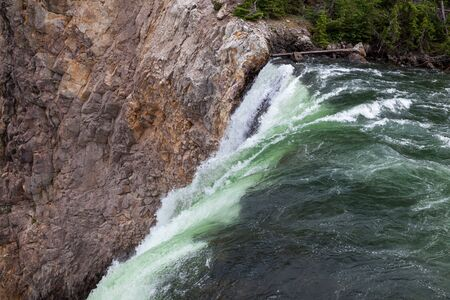 The top of Lower Falls in the Yellowstone River as the green water drops sharply off a cliff in Yellowstone National Park, Wyoming. Stok Fotoğraf