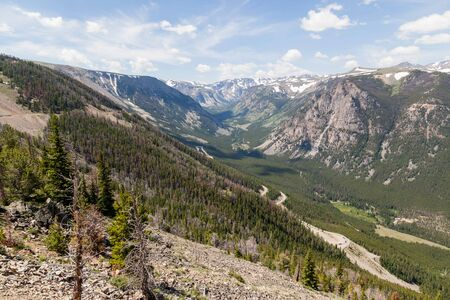 A landscape of Montana mountains still covered in patches of snow in summer as seen from the Beartooth Highway in Custer National Forest.