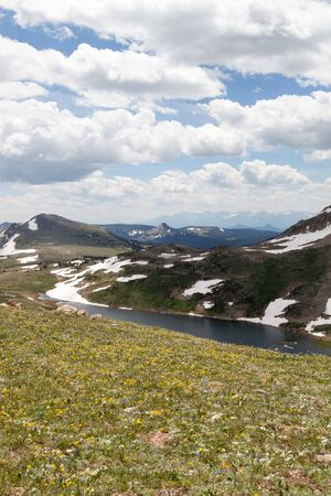 Gardner Lake deep in a valley between a steep mountain with patches of snow and a sloping hill covered in spring wildflowers.