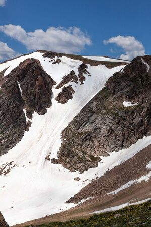 Snow covered mountain pass with trails from extreme snowboarders in the summer along the Beartooth Highway in Shoshone National Forest, Wyoming. Stok Fotoğraf