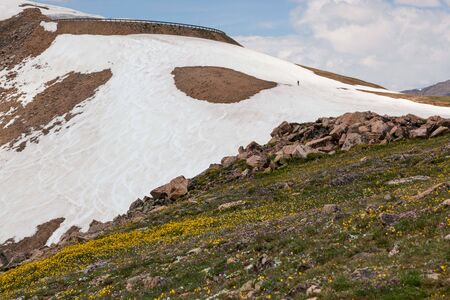 An unidentifiable man walking up a steep mountain to snowboard down the remaining summer snow along the Beartooth Highway in Shoshone National Forest, Wyoming.