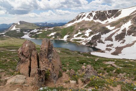 Gardner Lake behind large boulders in the ground and deep in a valley between a steep mountain with patches of snow and a sloping hill covered in spring wildflowers. Stok Fotoğraf
