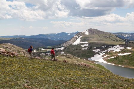 Two unidentifiable tourists hike across a beautiful landscape leading to Gardner Lake in the Shoshone National Forest, Wyoming. Stok Fotoğraf