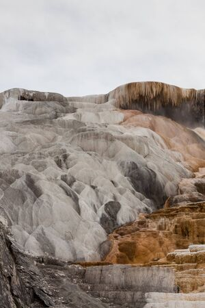 The travertine terraces of Mammoth Hot Springs with bright colors of bacteria in areas where the water is flowing and white and black surfaces on areas that are dry in Yellowstone National Park, Wyoming. 版權商用圖片