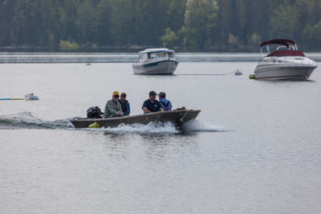 Grand Teton National Park, Wyoming / USA - July 17, 2014:  Four men in a small boat coming into Colter Bay Marina on Jackson Lake in the  Grand Teton National Park, Wyoming.