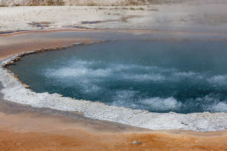 Deep blue boiling water inside of Crested Pool with a white rim at Yellowstone Natural Park.