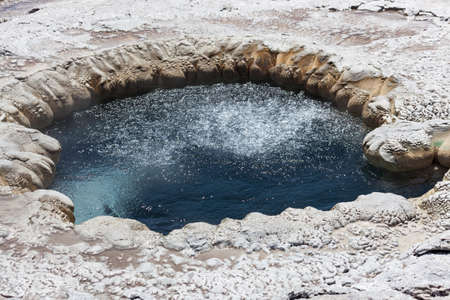 Beach Springs at Yellowstone National Park with bubbles in the hot water and steam rising up on a sunny summer day.
